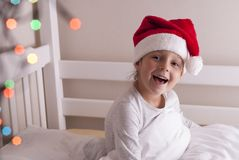 Girl in santa hat on the bed. Cute little girl in santa hat sits on the bed Stock Image