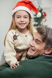 Girl In Santa Hat Being Carried By Father Royalty Free Stock Images