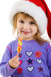 Girl in santa hat with a bright candy Royalty Free Stock Images