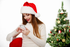 Girl in santa hat call phone by christmas tree Stock Photo