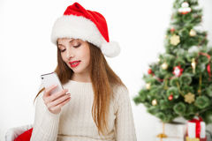 Girl in santa hat call phone by christmas tree Royalty Free Stock Photos