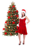Girl in santa hat by christmas tree. Stock Photography