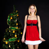 Girl in santa hat about christmas tree. Royalty Free Stock Photography