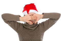 Girl in santa hat closes palms face. Stock Photography