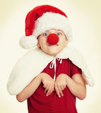 Girl in santa hat with clown nose on white isolated Stock Photos