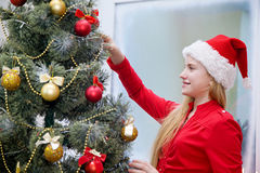 Girl in santa hat decorates a Christmas tree. With a smile on his face Stock Photos