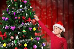 Girl in santa hat decorating christmas tree. With bauble Royalty Free Stock Images