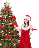 Girl in santa hat decoreting christmas tree. Royalty Free Stock Image