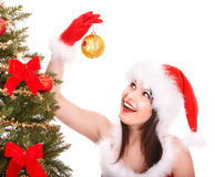 Girl in santa hat decoreting christmas tree. Royalty Free Stock Images
