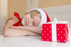 Girl in santa hat, dreaming about holiday gifts Royalty Free Stock Photography