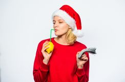 Girl santa hat drink juice lemon straw while hold pile of money. Symbol of wealth and prosperity. Christmas wishes. Rich. Girl with lemon and money. Woman lemon royalty free stock photo