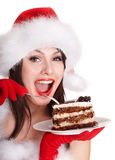 Girl in santa hat eat cake on plate. royalty free stock photo