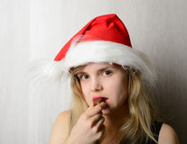 Girl in santa hat eating chocolate candy Stock Photo