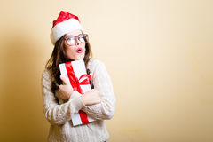 Girl in Santa hat excited holding giftbox on beige Royalty Free Stock Image