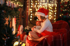 Girl in Santa hat with  favorite toy doll by  fireplace, Christm Stock Photos