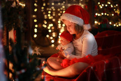 Girl in Santa hat with  favorite toy doll by  fireplace, Christm Royalty Free Stock Photography