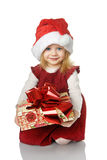 The girl in Santa hat with a gift. Royalty Free Stock Images