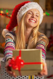 Girl in santa hat giving christmas present box Stock Photo
