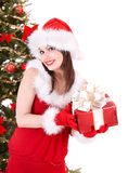 Girl in santa hat giving gift box. Stock Photos