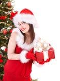 Girl in santa hat giving gift box. Stock Photos