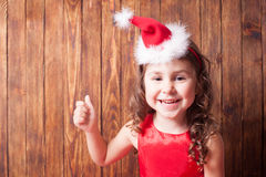 Girl in Santa hat headband. Is sitting over wooden wall and showing OK, copy space Stock Photo