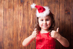 Girl in Santa hat headband. Is sitting over wooden wall and showing OK, copy space Stock Images