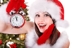 Girl in santa hat holding alarm o'clock. Royalty Free Stock Photography