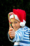 Girl in santa hat holding candy cane. Portrait of girl showing a candy cane Royalty Free Stock Photos