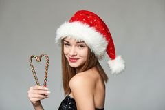 Girl in Santa hat holding Christmas candies in heart shape. Closeup of beautiful girl in Santa hat holding Christmas candies composed in heart shape Royalty Free Stock Photos