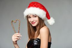Girl in Santa hat holding Christmas candies in heart shape. Closeup of beautiful girl in Santa hat holding Christmas candies composed in heart shape Stock Photo