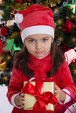 Girl in Santa hat holding Christmas gift royalty free stock image