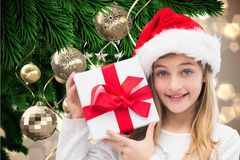 Girl in santa hat holding christmas gifts Royalty Free Stock Images