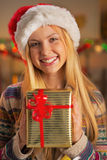 Girl in santa hat holding christmas present box Stock Photos
