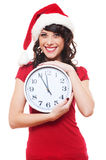 Girl with santa hat holding clock Royalty Free Stock Photos