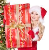 Girl in santa hat holding gift box. Girl in santa hat holding  gift box by christmas tree. Isolated Stock Photo