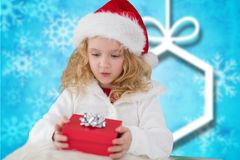 Girl in santa hat holding a gift box. Against digitally generated background Stock Images