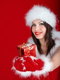 Girl in Santa hat holding gift box on red background. Royalty Free Stock Image