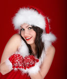 Girl in Santa hat holding gift box on red background. Stock Photos