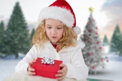 Girl in santa hat holding a gift. During christmas time Stock Images