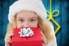 Girl in santa hat holding a gift. Portrait of girl in santa hat holding a gift during christmas time Royalty Free Stock Photo