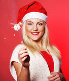 Girl in Santa hat holding sparklers Royalty Free Stock Photos
