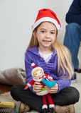 Girl In Santa Hat Holding Toy. Full length portrait of girl in Santa hat holding toy at home Royalty Free Stock Photos
