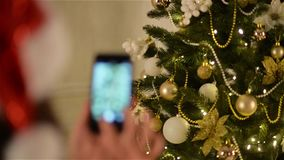Girl in Santa Hat Holds the Smartphone in Her Hand and Takes Photo of Christmas Tree. Beautiful Decoration of Xmas. Spruce, HD stock video