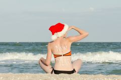Girl in Santa hat with the inscription New Year on the back is sitting on the beach and looks into the distance.  Stock Images