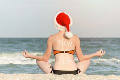 Girl in a Santa hat with an inscription New Year on her back sitting on the beach in a lotus pose. Back view Royalty Free Stock Photos