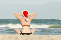 Girl in a santa hat with an inscription New Year on her back sitting on the seashore Royalty Free Stock Photo