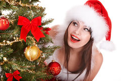 Girl in santa hat look at christmas tree. Stock Image