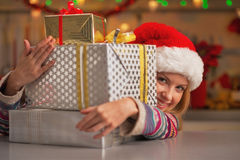 Girl in santa hat looking out from stack of christmas present Royalty Free Stock Photography