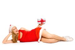 Girl in Santa hat lying down with gifts royalty free stock image
