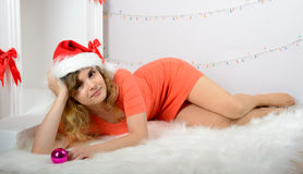 Girl in santa hat lying near the fireplace Royalty Free Stock Image